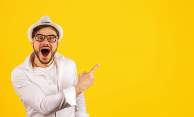 Happy hipster pointing up on yellow Wall mural
