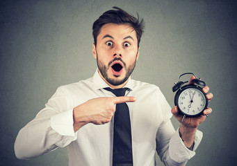 Scared man pointing at alarm clock