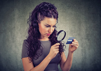 Curious woman looking at credit card through magnifying glass