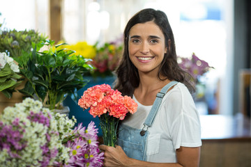 Smiling woman selecting flowers at florist shop