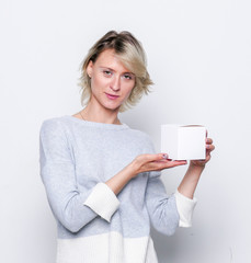 Happy girl with small white gift box. Small gift in the hands of a woman indoor.