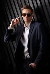 Fashion business man in suit posing in trendy eyeglasses on black studio wooden background. Closeup portrait