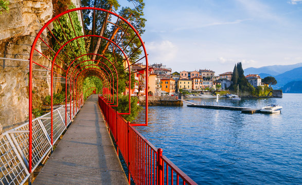 Red garden arch on coastline leading towards the beautiful and historic city of Varenna on the edge of Lake Como in the northern Italian region of Lombardy