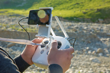 Man with remote control prepare white drone with digital camera for start flying in winter. Camera flying in sky over mountain Drone with high resolution digital camera. Operation of drone in air