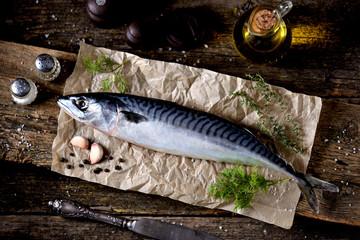 Fresh raw mackerel on an old wooden background.
