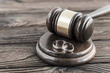 hammer of a judge, a pair of wedding rings on a wooden background. family conflicts. marriage contract