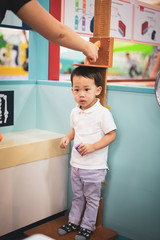 A boy is measuring height and weight.