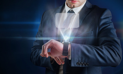 Composite image of businessman using hologram watch against futuristic glowing black background