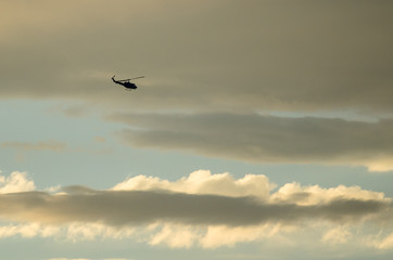 Silhouetted Helicopter Flying Across a Sunset Sky