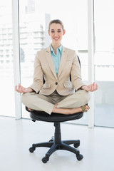 Beautiful classy woman sitting in lotus position on her swivel chair