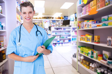 Smiling nurse holding clipboard  against close up of shelves of drugs