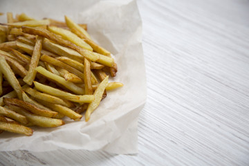 French fries on white wooden background, close up.