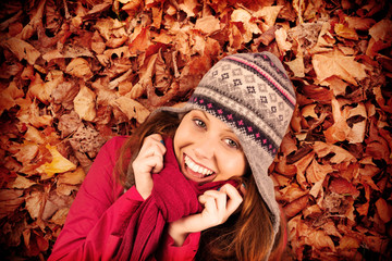 Cold redhead wearing coat and hat against autumn leaves on the ground