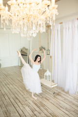 Young pretty ballerina is dancing near swing in studio with light interior