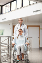 Patient sitting on a wheelchair next to a doctor