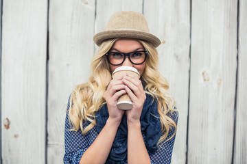 Smiling fashionable blonde drinking coffee outdoors