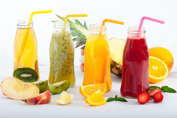 Bootles with pineapple, strawberry and orange Detox juices . Ripe fruit full of vitamins.