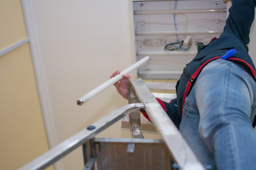 Electrician man worker in uniform installing ceiling fluorescent lamp