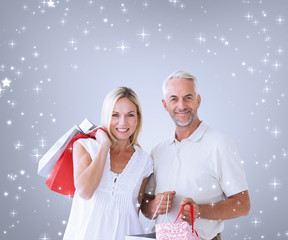 Composite image of happy couple with shopping bags against grey vignette