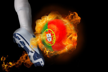 Football player kicking flaming portugal ball against black