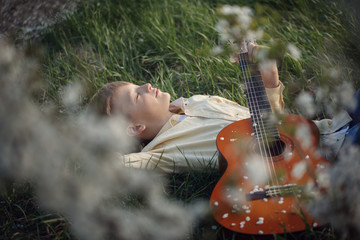 Cute boy lies on the grass with a guitar on sunset