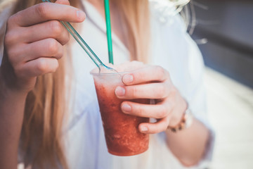 Young stylish woman in a summer hott city street drinking Fruit smoothie - healthy eating concept.