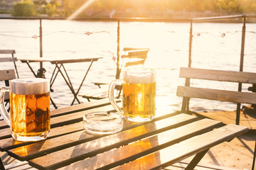 Two glasses of light beer with foam on a wooden table.On a boat. Garden party. Natural background. Alcohol. Draft beer. Landscape, golden.