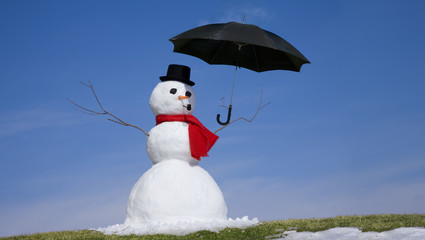Snowman in the green grass of spring holding an umbrella