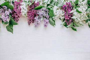 Wall Murals Lilac Beautiful white and violet lilac flowers branches on the white wooden background, mock up top flat view
