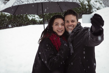 Couple taking selfie on mobile phone during snowfall