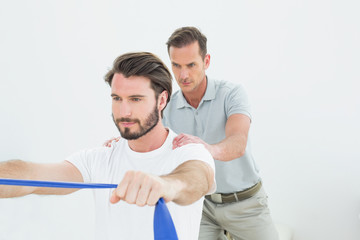Male therapist assisting a young man with exercises