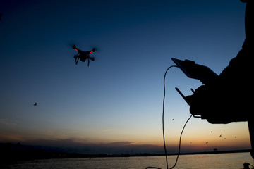 Flying with the drone. silhouette against the sunset sky