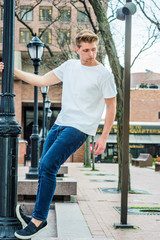 Young Man Summer Street Casual Fashion in New York, wearing white T shirt, blue jeans, black casual shoes, standing on black light pole, looking down..