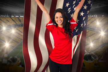 Cheering football fan in red holding usa flag against vast football stadium with fans in yellow