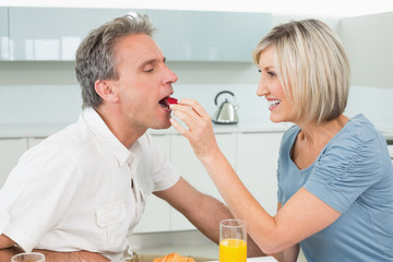 Loving woman feeding man in the kitchen