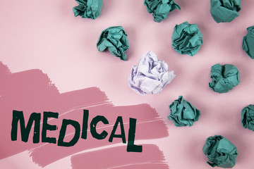 Handwriting text Medical. Concept meaning Related to science of Medicine Treatment for illness or injuries written on Painted Pink background Crumpled Paper Balls next to it.