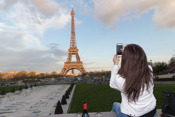 Woman taking photo of Eiffel Tower in Paris, France with cellphone