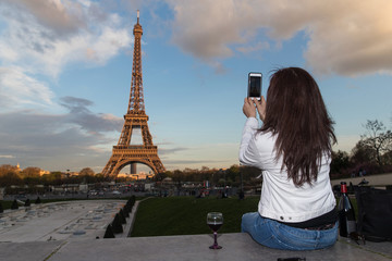 Woman taking a photo of the Eiffel Tower with cellphone