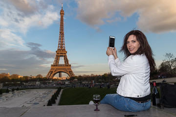 Woman taking photo of Eiffel Tower with her smartphone
