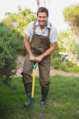 Happy man in dungarees raking the garden