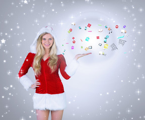 Composite image of Pretty girl presenting in santa outfit against grey vignette