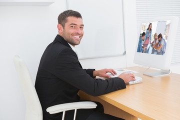 Team having meeting with one woman smiling at camera against smiling businessman working at a desk
