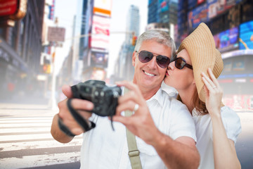 Vacationing couple taking photo against blurry new york street