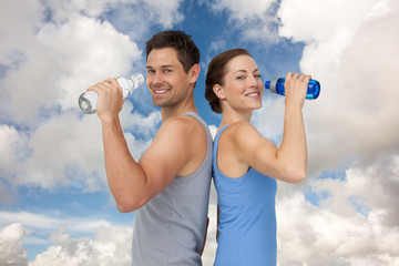 Happy fit young couple with water bottles against blue sky with white clouds