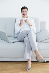 Full length of a smiling well dressed woman with laptop and coffee cup on sofa
