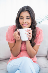 Pleased cute brunette sitting on couch holding mug