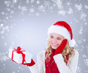 Happy festive blonde with gift against grey vignette