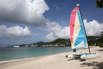 Beautiful Grand Anse beach with St Georges in the background & colorful boat in the foreground, Grenada, Caribbean.
