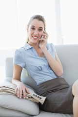 Pretty classy businesswoman phoning while sitting on couch
