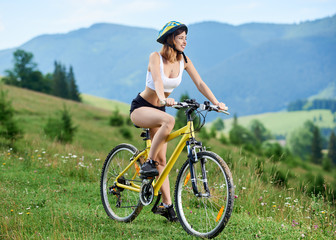 Active young female cyclist riding on yellow bicycle on a rural trail in the mountains, wearing helmet, enjoying valley view. Mountains, forests on the background. Outdoor sport activity